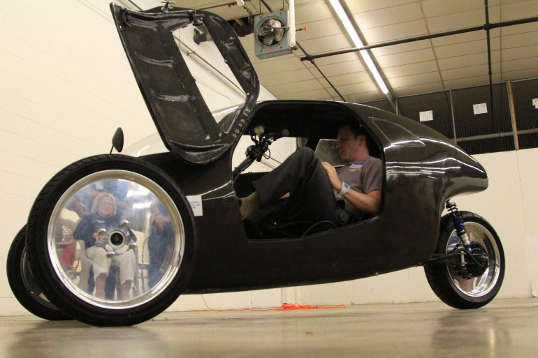 "Raht Racer-  ""an electric-assist velomobile that amplifies the rider's pedaling power, reportedly allowing them to move as fast as the cars around them."""